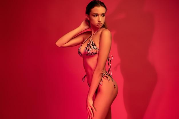 Meisje in zomer bikini poseren op karmozijnrode oppervlak in studio