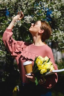 Meisje in zonnebril en een roze trui met een boeket van gele tulpen en koffie onder bloeiende bomen