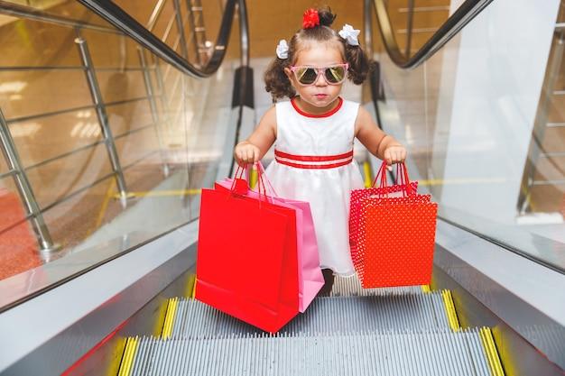 Meisje in zonnebril op de roltrap in het winkelcentrum met aankopen