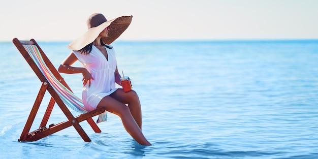 Meisje in zonnehoed en tuniek zittend op de strandstoel aan zee terwijl ze cocktail zomervakantie houdt