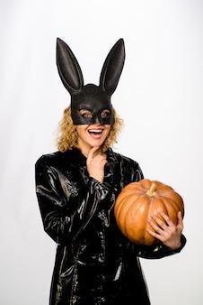 Meisje in zwart konijnenmasker met pompoen oktober halloween kostuum sexy meisje in konijnenmasker met jack o