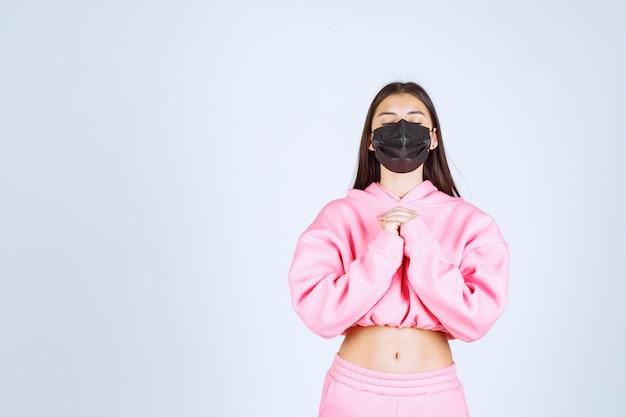 Meisje in zwart masker dat haar handen verenigt en bidt.