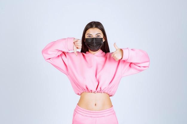 Meisje in zwart masker met duim op en neer borden.