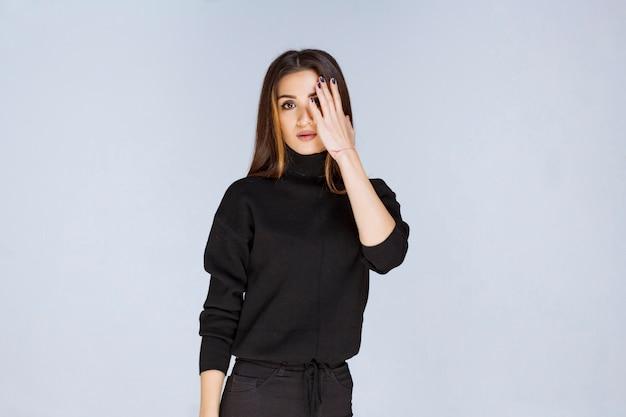 Meisje in zwart overhemd dat door haar vingers kijkt. hoge kwaliteit foto