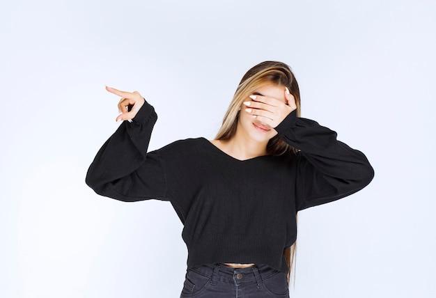 Meisje in zwart overhemd dat haar ogen sluit en slepping.