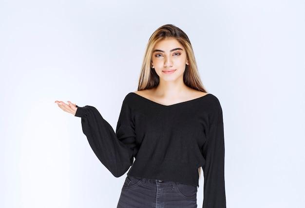 Meisje in zwart overhemd dat hand opent en iemand voorstelt.