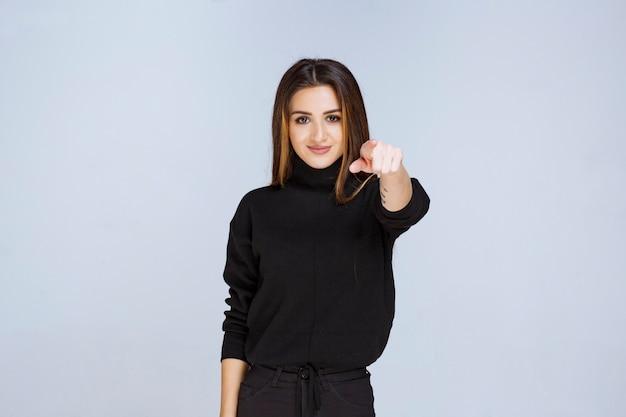 Meisje in zwart overhemd dat iemand vooruit wijst. hoge kwaliteit foto