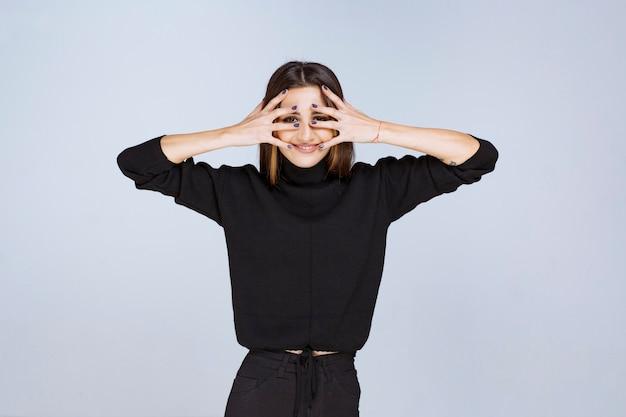 Meisje in zwart overhemd dat over haar vingers kijkt. hoge kwaliteit foto