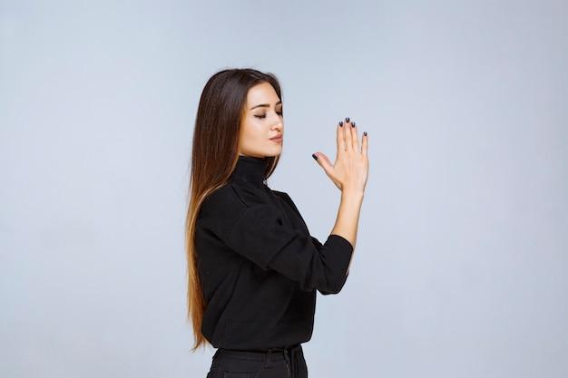 Meisje in zwart shirt dat haar handen verenigt en bidt. hoge kwaliteit foto