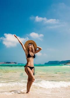 Meisje in zwarte bikini en met hoed op strand balos