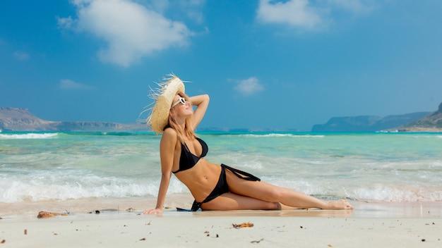 Meisje in zwarte bikini en met hoed op strand van balos
