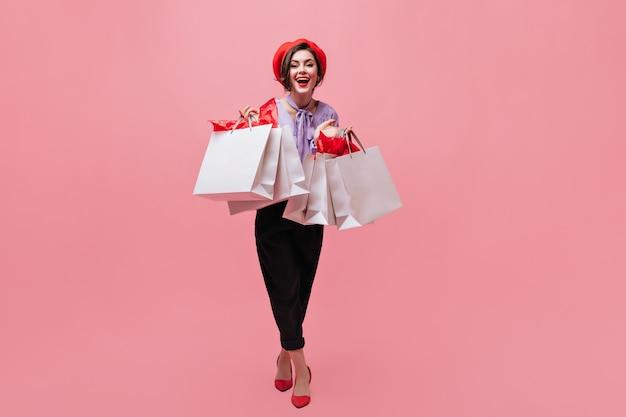 Meisje in zwarte broek en rode baret houdt verschillende pakketten en glimlacht op roze achtergrond.