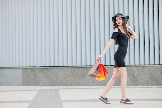 Meisje in zwarte jurk buiten lopen
