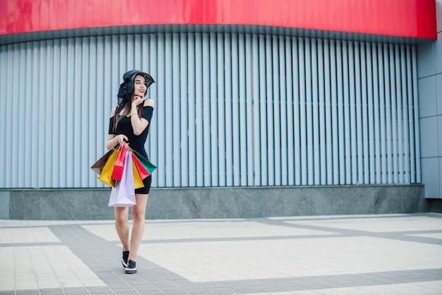 Meisje in zwarte jurk die boodschappentassen draagt