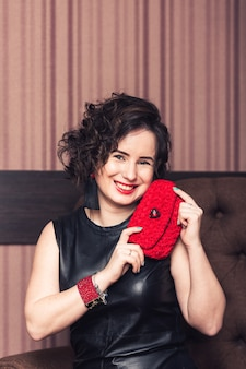 Meisje in zwarte jurk met handgemaakte rode armband, zwarte gebreide oorbellen en tas