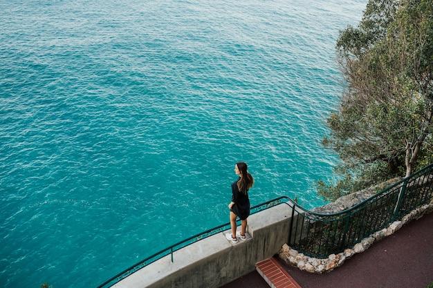 Meisje in zwarte jurk staande op de steen in de buurt van zee met azuurblauw water