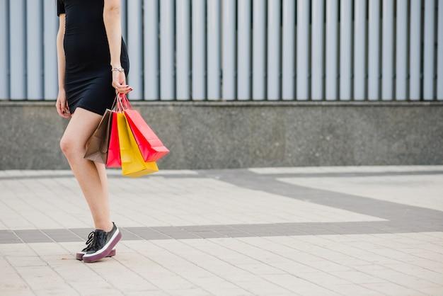 Meisje in zwarte jurk staande zakken