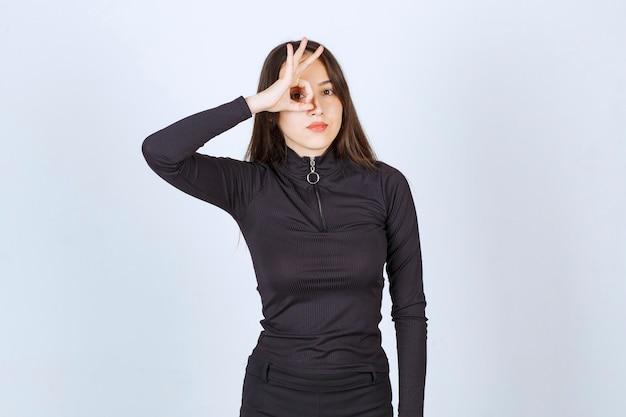 Meisje in zwarte kleding die het teken van het cirkelgenot tonen.