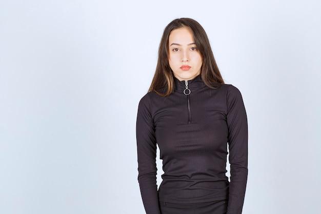 Meisje in zwarte kleding geeft professionele en neutrale poses zonder reactie.