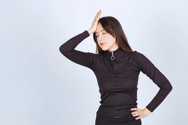 Meisje in zwarte kleding kijkt boos en boos.