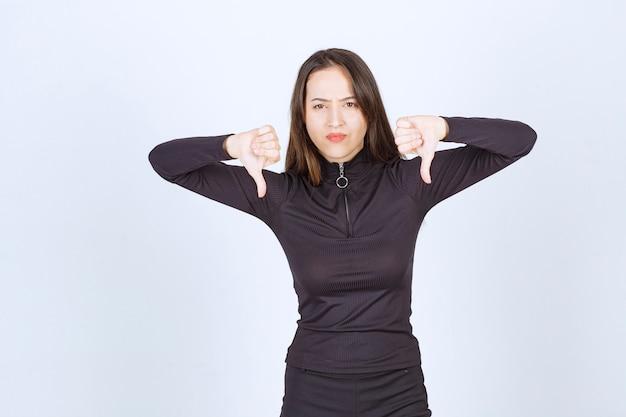 Meisje in zwarte kleding met duim omlaag teken.