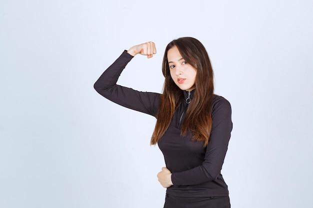 Meisje in zwarte kleding met haar vuist- en armspieren.