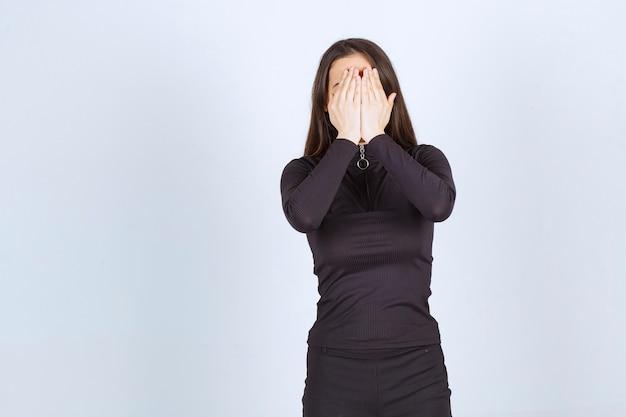 Meisje in zwarte kleren die haar gezicht of ogen bedekken.