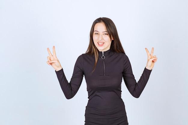 Meisje in zwarte kleren die vrede en vriendschapsteken tonen.