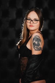 Meisje in zwarte lingerie en bril met een tatoeage op zijn arm poseren