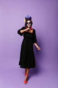 Meisje in zwarte midi-jurk loopt tegen paarse muur. model met schedelmasker op gezicht vormt voor halloween-foto.