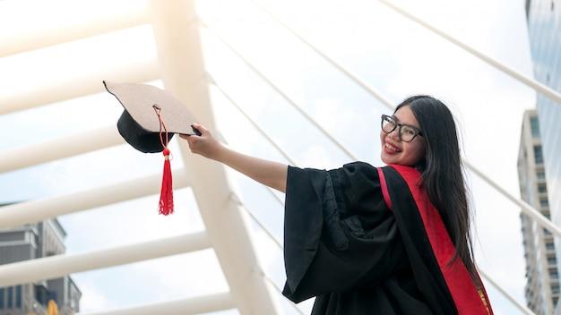 Meisje in zwarte toga's en houd diploma certificaat lachend met gelukkig afgestudeerd.
