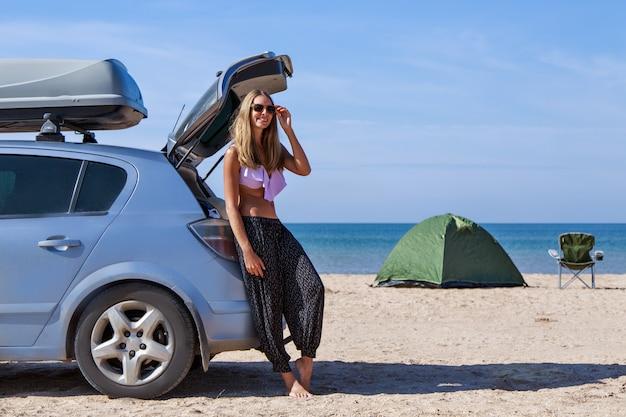 Meisje in zwembroek en lange broek poseren bij haar auto op het strand met een kampeertent op de achtergrond