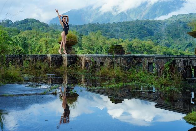 Meisje in zwembroek in het mystieke verlaten rotte hotel in bali met blauwe lucht