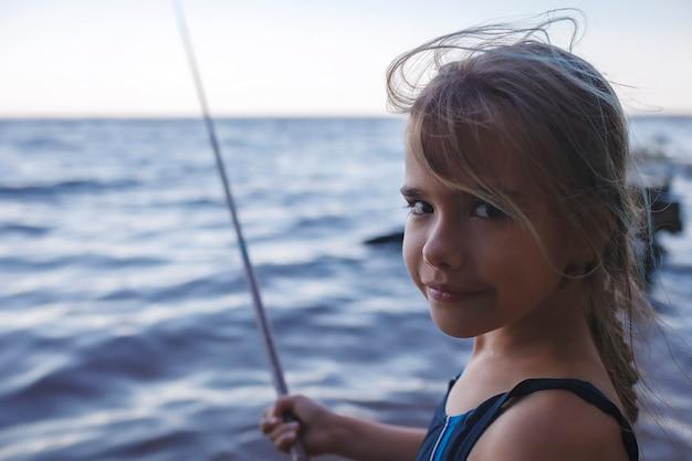 Meisje in zwemkleding vissen vanaf zee strand in de vroege ochtend blauwe uren actief weekend kamperen