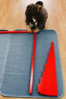Meisje is een klas van een school die de rode balken montessori op een mat plaatst.