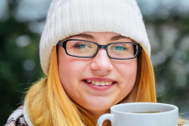Meisje is in de winter door sneeuw en houdt een mok hete thee vast. natuurlijk licht, lichte achtergrond