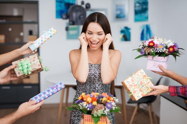 Meisje is omgeven door geschenken. ze staat in het midden.
