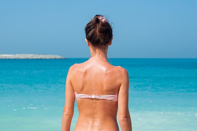 Meisje is terug in een zwembroek tegen de muur van de zee en de blauwe lucht