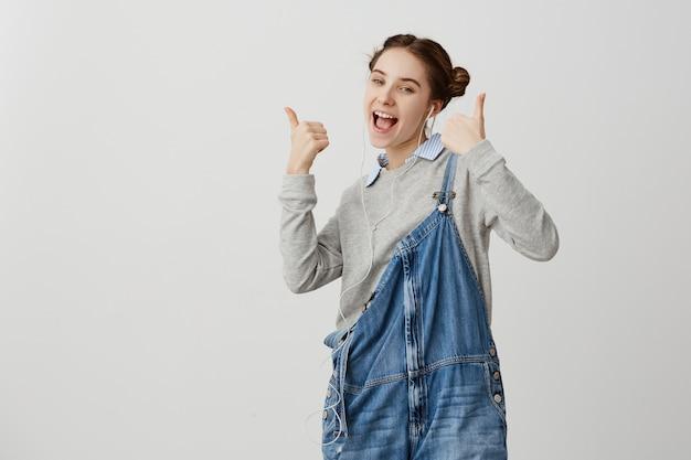 Meisje jaren '20 in denim die gelukkige gebaren duimen omhoog over witte muur zijn. vrouwelijke infantiele schrijfster viert het succes van haar nieuwe boek en luistert het in elektronische versie via oortelefoons. techniek concept