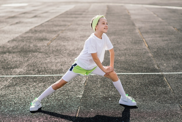 Meisje joggen op een zonnige zomeravond, opleggen van loopband, stadion, fysieke training, terug naar school.