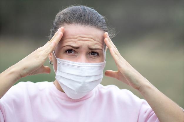 Meisje, jonge vrouw in paniek in beschermend steriel medisch masker op haar gezicht dat haar hoofd met handen houdt, die hoofdpijn heeft. luchtverontreiniging, symptomen van virus, pandemisch coronavirusconcept. covid-19