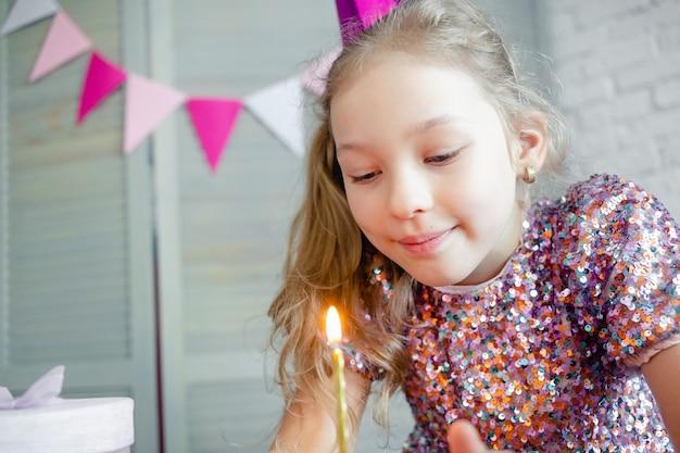 Meisje kaarsjes op de verjaardagstaart uitblazen