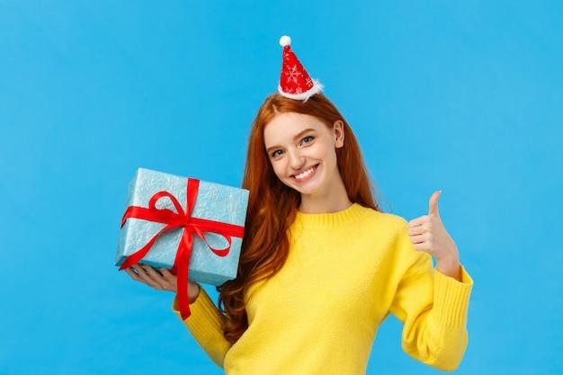 Meisje kan je cadeau gemakkelijk inpakken. blij en assertief mooie roodharige vrouwelijke winkelmedewerker helpt de klant, toont een duim omhoog, helemaal klaar of een goed gebaar, een glimlachende doos met geschenken