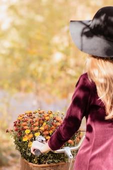 Meisje keerde haar in de herfst op een fiets de rug toe