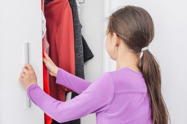 Meisje kiest kleding voor school