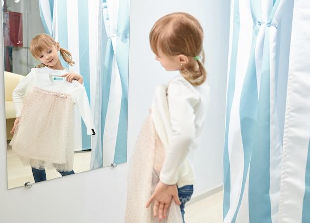 Meisje kiezen, die kleding in wandelgalerij proberen, die spiegel bekijken.