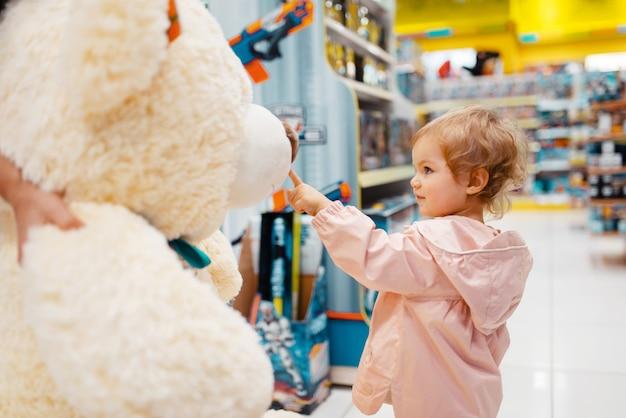 Meisje kiezen grote teddybeer in kinderwinkel, zijaanzicht.