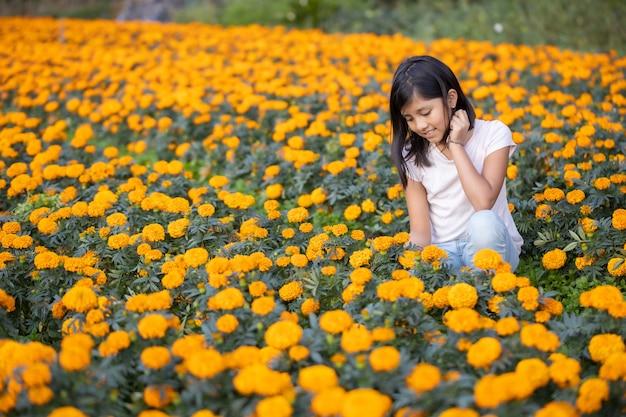 Meisje kijken en glimlachen naar cempasuchil bloemen op het veld