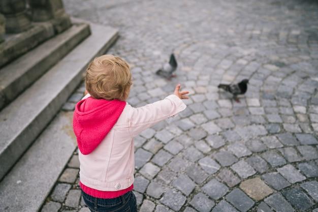 Meisje kijken naar duiven op het plein