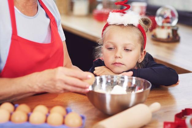 Meisje kijken naar grootmoeder die een cake maakt